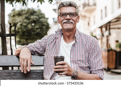 Good day! ?heerful senior man relaxing on park bench and drinking coffee on a summer's day.