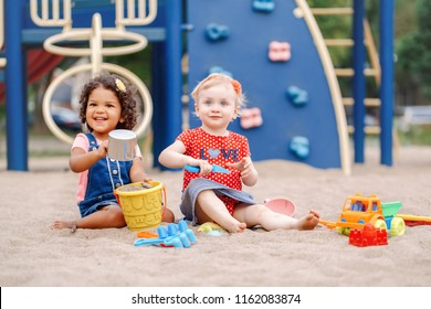 Good day. Two cute Caucasian and hispanic latin babies children sitting in sandbox playing with plastic colorful toys. Little girls friends having fun together on playground.