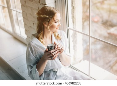 Good day. Woman near window with cup. Dream and relax.
