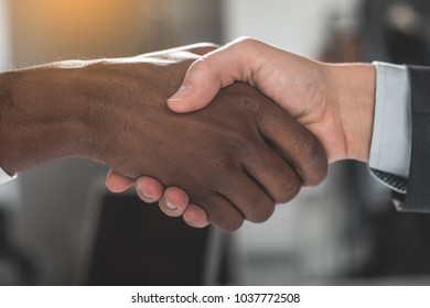 Good deal. Close up of firm strong handshake of business partners in office
