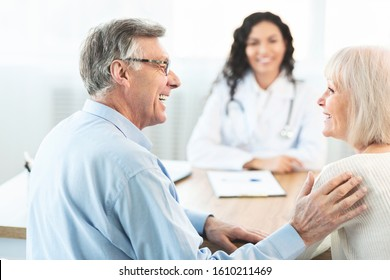 Good Diagnosis. Happy elderly couple looking at each other during consultation with female doctor at clinic, free space