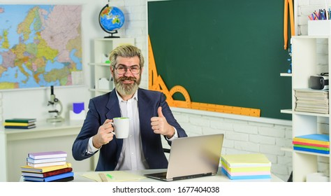 Good drink for good work. Bearded man with cup give thumb up. Senior teacher drink coffee in class. Hot caffeine drink. Tasty drink recipe. School break. Breaktime. Learning and teaching.