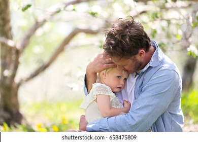 A Good Father is holding and comforting his sad and pouting baby daughter outside on a spring day.