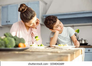 Good food. Alert dark-haired young mom smiling and having healthy breakfast with her son and the boy looking at the vegetable on his fork