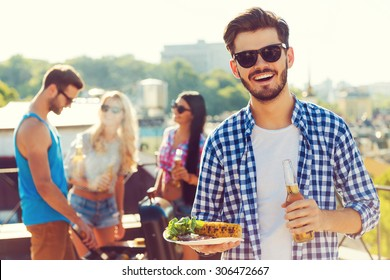 Good food with best friends. Smiling young man holding bottle with beer and plate with food while three people barbecuing in the background