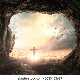 Good Friday concept: Empty tomb stone with cross on meadow sunrise background