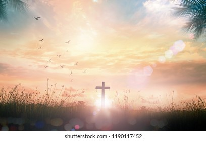 Good Friday concept: Silhouette cross on meadow autumn sunrise background