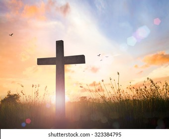 Good Friday concept: Silhouette cross of Jesus Christ on meadow autumn sunrise background