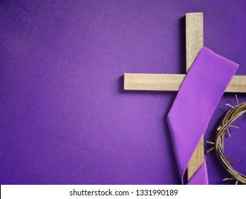 Good Friday, Lent Season and Holy Week concept - A religious cross and a woven crown of thorns on purple background.