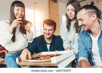 Good friends at home party. Group of four people eating pizza from delivery box and taking picture of food using mobile phone camera