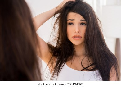 Good morning? Frustrated young woman looking at her reflection in the mirror and holding hand in hair