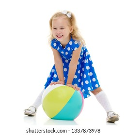 A good girl is playing with a big inflatable ball. The concept of a happy childhood, recreation in nature, exercise. Isolated on white background.