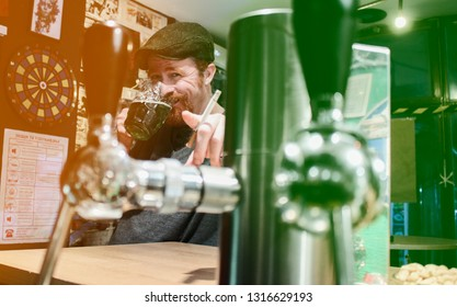 Good guy Irish smokes cigarette and drink beer and calling zou to join in pub during St Patrick Day (filter represent Irish flag)