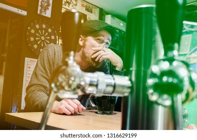 Good guy Irish smokes cigarette and drink beer in pub during St Patrick Day (filter represent Irish flag)