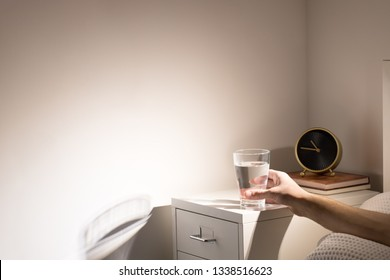 Good habit - drinking a glass of water before going to sleep. Man in bed taking glass of water from bedside table before bedtime, copy space.