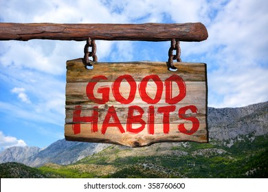 Good habits motivational phrase sign on old wood with blurred background