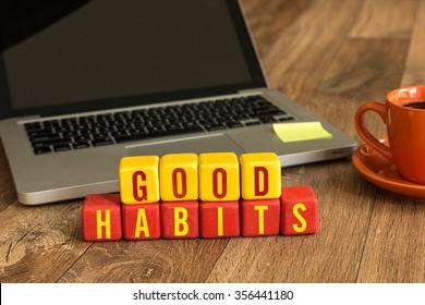 Good Habits written on a wooden cube in a office desk