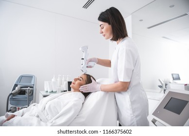 I am in good hands. Side view of smiling woman laying at daybed with closed eyes. Beautician in lab coat using automatic syringe gun