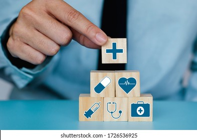 Good Healthcare and Insurance concept.Business hand choose plus sign on wood cube block,Positive quantity,Take care and Safety.