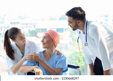 Good hospital provide quality medical service. Professional doctor, nurse take care a patient.  Senior Caucasian woman cover head with a cloth caused of chemotherapy cancer, smiling sitting wheelchair