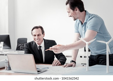 Good idea. Delighted worker standing in semi position and raising hand while pointing on laptop