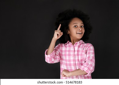Good idea! Pretty mulatto girl pointing up while standing against blackboard. Copy space