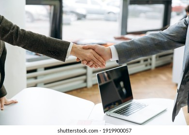 Good job. Close-up of male and female hands, making shaking hands gesture on business briefing meeting, sign an important contract, coming to agreement after negotiations