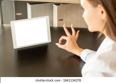 Good job. Ok gesture. Online conference. Distance teamwork. Woman showing approval sign tablet computer blank screen on wooden table workplace interior back view.