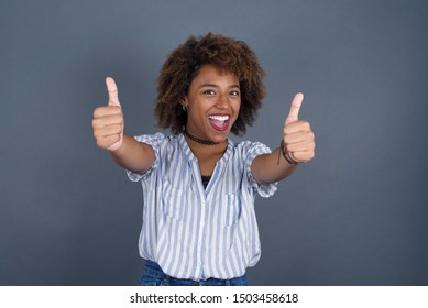 Good job! Portrait of a happy smiling African American young successful woman giving two thumbs up gesture standing indoors. Positive human emotion facial expression body language.