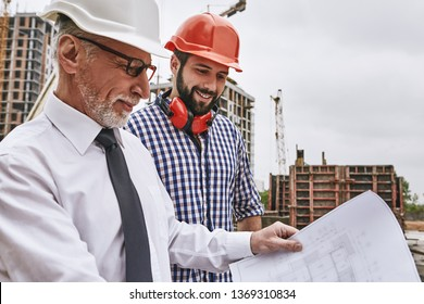 Good job! Side view of senior architect in formal wear and white helmet holding construction drawing and discussing it with young cheerful builder while standing against construction site.