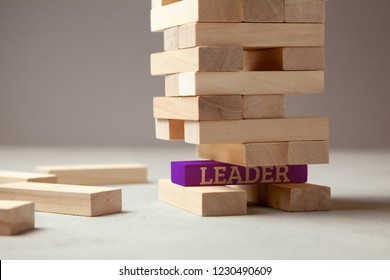 Good leader is building successful team and company in business. Tower of wooden blocks with the inscription leader