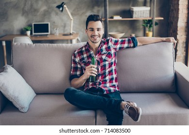 Good life. Chilling, calmness, enjoying free time alone. Young brunet hipster with bottle of beer at home, sitting on couch in casual smart, trendy fashionable shoes. Pause, break, recreational time.