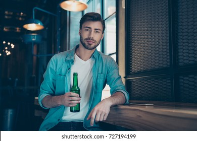 Good life. Chilling, calmness, enjoying free time alone. Young brunet hipster with bottle of beer at the bar, sitting in casual smart, trendy and fashionable. Pause, break, recreational time