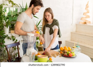 good loking man and woman making salad from different fruits. close up photo. wellness, wellbeing. copy space