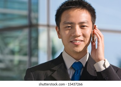Good looking asian business man standing with formal suit and mobile phone.