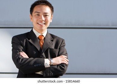 Good looking asian business man standing with formal suit.