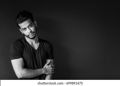 Good looking and attractive sexy male model with dark black hair and a gym fit muscled body, is posing single in front of a dark wall