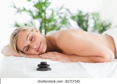 Good looking blonde woman lying on a lounger with eyes closed in a wellness center