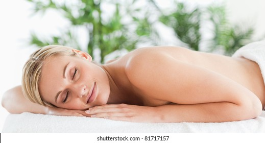 Good looking blonde woman sleeping on a lounger in a wellness center