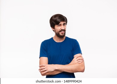 Good looking brunet man in a blue shirt holding arms folded over his chest with sceptical emotion standing isolated over white background. Concept of doubt.
