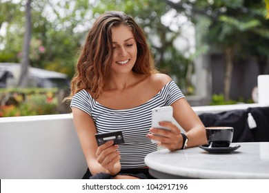 Good looking brunette female in fashionable t shirt uses online banking on smart phone to transfer money from credit card, connected to free wifi in coffee shop. People and ecommerce concept