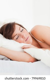 Good looking brunette female having a rest while lying on a bed