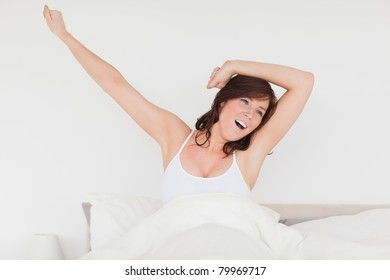 Good looking brunette woman posing while stretching on a bed