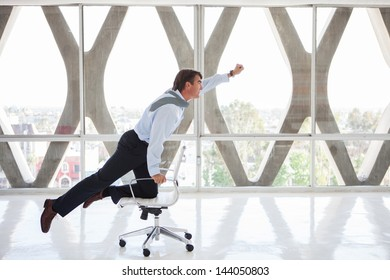 Good looking Business man Flying on a chair as if to be superman