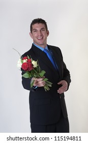 good looking business man holding a bunch of flowers for someone special