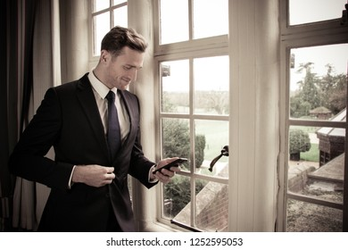 Good looking businessman standing next to large window using mobile phone