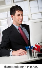 A good looking businessman using the computer in his office