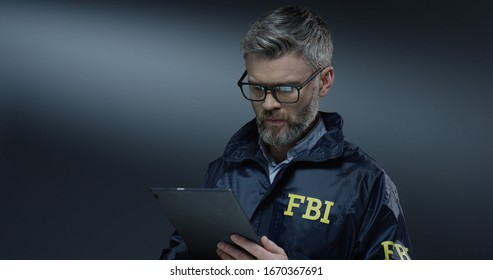Good looking Caucasian grey-haired male FBI policeman in glasses tapping and scrolling on the tablet device while browsing.