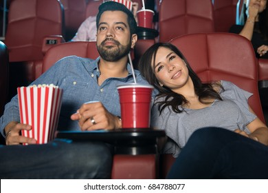 Good looking couple having a good time together during a date at a movie theater