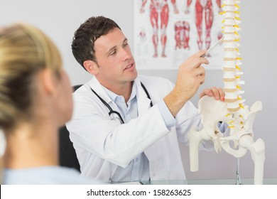 Good looking doctor showing a patient something on skeleton model in bright office